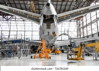 Large passenger aircraft on service in an aviation hangar rear view of the tail, on the auxiliary power unit