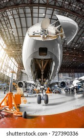 A large passenger aircraft on the service in the aviation hangar view the nose and radar under the hood, the front chassis riser