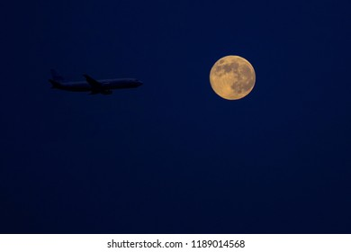 large passenger plane in the night sky against the background of the full moon