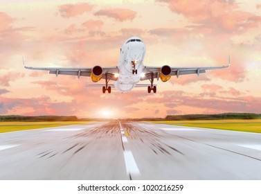 Large passenger plane take off from the runway before the light from the sunshine