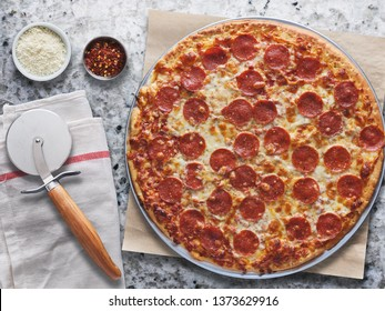 large pepperoni pizza on marble counter in overhead flat lay composition