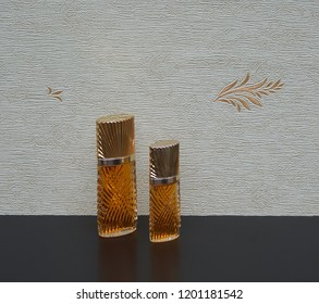 large perfume bottle next to a commercial perfume bottle in front of the satin wallcovering Elysee
