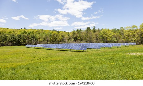 A large photo of many solar panels in a bright green field with blue sky.