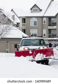 A large pickup truck with a snow plow clearing a dryway in aparment complex.