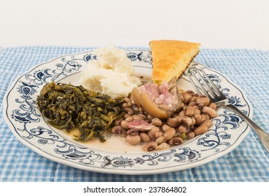 Large piece of fat ham hock in black-eyed peas with collard greens and mashed potatoes and slab of cornbread.