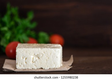 Large piece of feta cheese on dark wooden table. Selective focus.