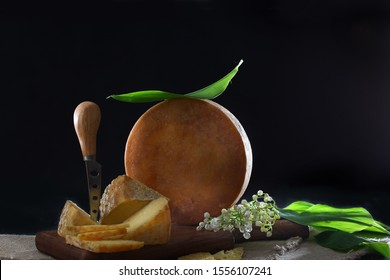 A large piece of hard cheese is cut into a cheese knife. Lilies of the valley and cheese. Copy space. The concept of homemade cheese.