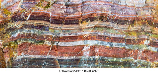 A large piece of raw agate. The semi-precious stone is banded and shows many, intense colors. Concept: rocks and minerals