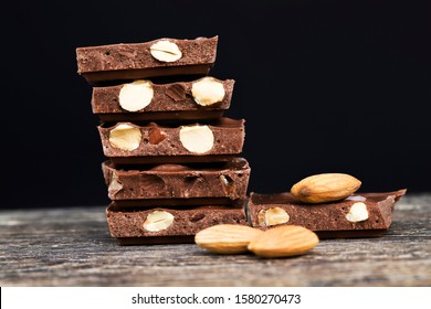large pieces of chocolate with roasted almond kernels on a wooden table, close-up of natural cocoa products and nuts