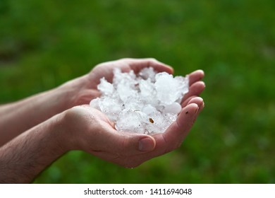 large pieces of ice hail in the palm of your hand. man holding a handful of large hailstones. consequences of natural anomalies.