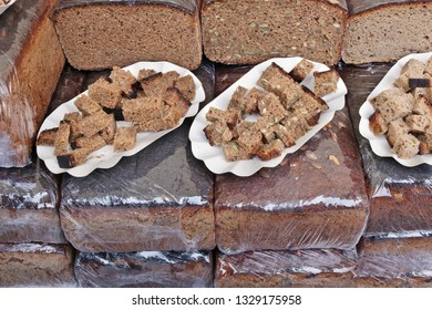 Large pieces of Lithuanian rustic rough rye black bread are sold on the street during the national spring fair