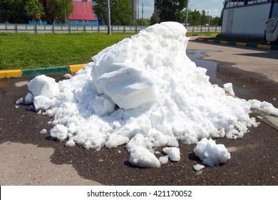A large pile of dirty snow lying in the puddle on the asphalt road on background green grass and white fence (global warming)