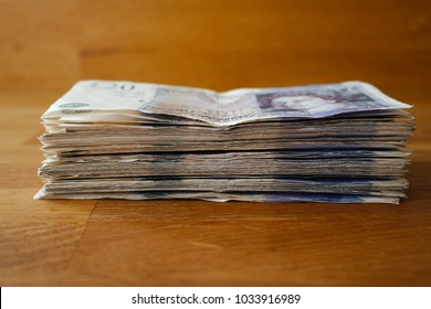A large pile of money in bank notes, giving the impression of wealth.