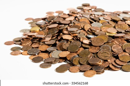 A large pile of old, dirty coins - mostly American pennies - on a clean white surface under bright lighting.