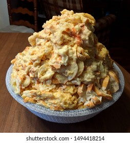 A large pile of orange a cream colored chunks and pieces of pawpaw fruit mash heaped in a cheesecloth covered bowl on a brown wooden table