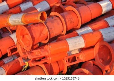 Large pile of orange and white reflective traffic safety construction channelizing cones with loops on top.