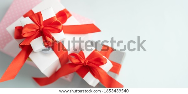 A large pile of pastel-colored packaged gift boxes with bright red ribbons and bows, isolated on a light background. Gift concept for girls.