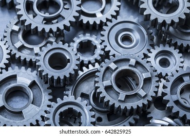 A large pile of steel gears on a sheet of industrial metal.