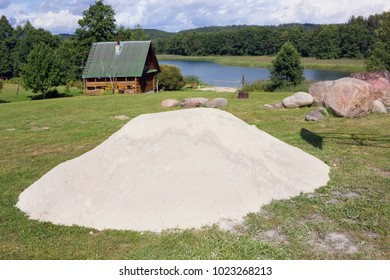A large pile of white clean river sand lies on a lawn  near a forest village. Sunny summer august day nature landscape
