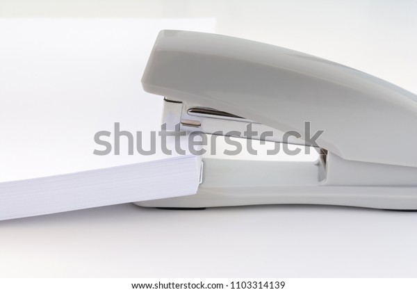 a large pile of white paper is placed in a small office stapler, concept abstract background