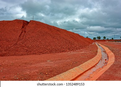 Large piles of bauxite ore, which is refined into aluminum, sit at a treatment area storage of bauxite. Guinea, Africa.