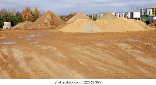 A large piles of construction sand with traces of tractor wheels on city building site. Panoramic collage from several outdooe shots