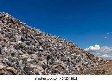 Large piles of granite boulders and lots of small, high heaps with a sky as a backdrop.