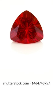 A large pincushion triangle faceted mexican fire opal shown on a white background. The stone is mostly red in color.