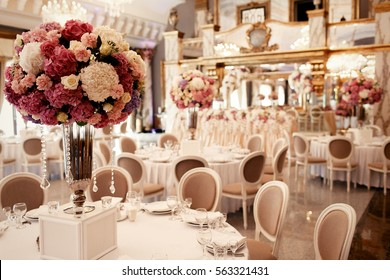 Large pink bouquet of hydrangeas and roses stands on dinner table in luxurious hall