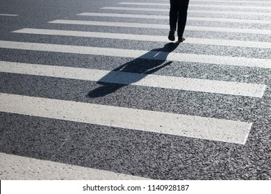 Large plans for road markings crossing the street. Dark gray asphalt, wide white stripes. Nobody here. Safe crossing across the road.