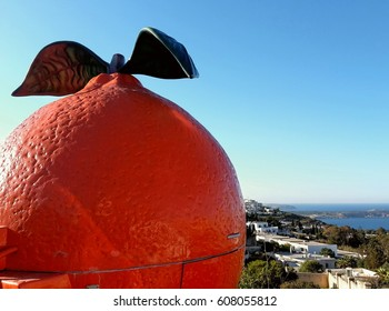 Large plastic orange and a view down into a mediterranean landscape and to the  sea