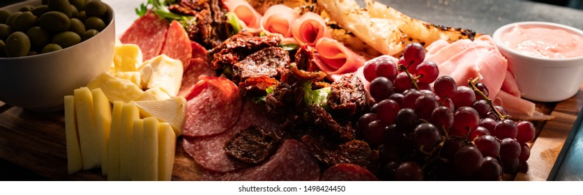 Large platter of delicious grazing gourmet food prepared by chef in a restaurant served on a wooden board