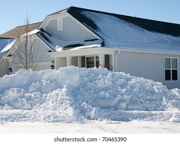 A large plowed pile of snow in front of a house on the corner after the 2011 blizzard in the midwest