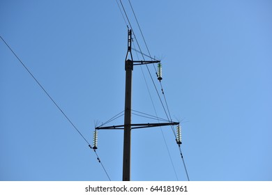 A large pole with electric wires on blue sky background
