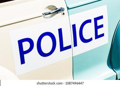 Large police sign on the side of a vintage patrol car.