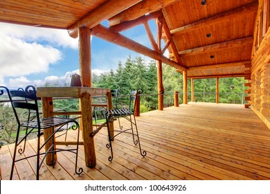Large Porch of the log cabin with small table and forest view.