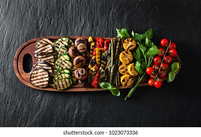 a large portion of colored grilled vegetables and mushrooms on a wooden tray on a dark slate. festive summer food