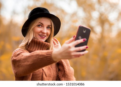 large portrait. beautiful young smiling blonde girl in a brown warm sweater, black felt hat makes selfie on a cell phone. In the background autumn trees. horizontal photo in the park