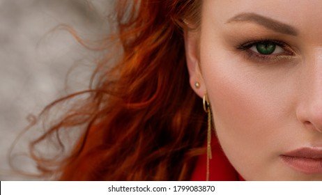 A large portrait of a young red-haired woman with bright makeup and green eyes. Part of the face close up