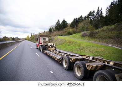Large powerful big rig semi truck with a trailer for transportation of oversized heavy cargo and objects. Trailer with a step down for the transport of high loads. Semi truck drive on green highway.