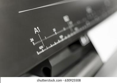 Large printer format inkjet working. Ink jet plotter printing unrecognizable document. Focus on ruller showing A1 huge format dimension