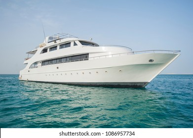 Large private luxury motor yacht boat sailing out on a tropical sea