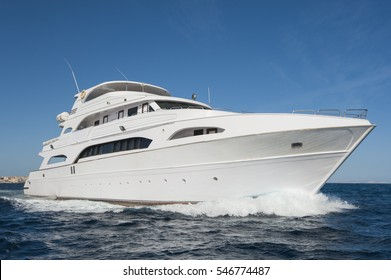 A large private motor yacht under way sailing out on tropical sea