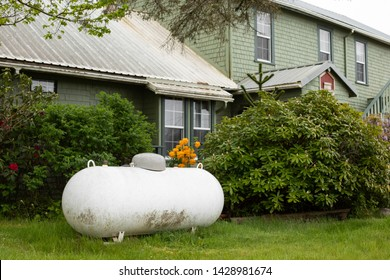 Large propane tank in the yard of a rural home, with a house in the background and space for text on the right