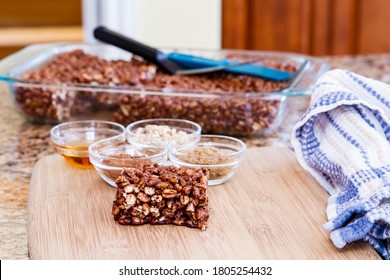 Large puffed wheat square treat with small glass bowls of raw ingredients beside; delicious and chewy puffed wheat squares