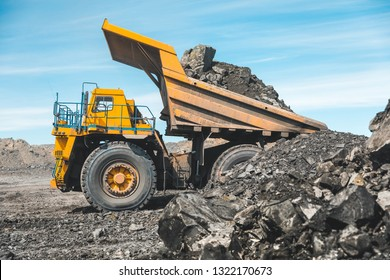 Large quarry dump truck. Loading the rock in dumper. Loading coal into body truck. Production useful minerals. Mining truck mining machinery, to transport coal from open-pit as the Coal Production