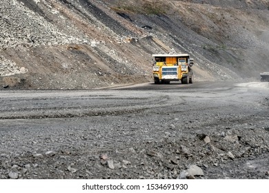 Large quarry dump truck. Transport industry. A mining truck is driving along a mountain road. Quarry truck carries coal mined.