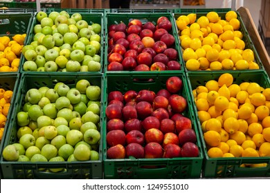 A large rack with baskets with different types of apples and lemons in the fruit department of the shopping center. Fresh and healthy foods for every day diet.