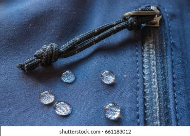 large rain drops dew on dark waterproof weatherproof membrane clothes. closeup macro shot of buckle, zipper, sealed pocket, fastener