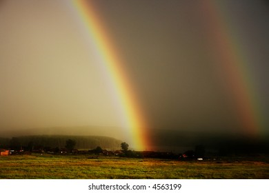 Large rainbow during thunderstorm over farmers field